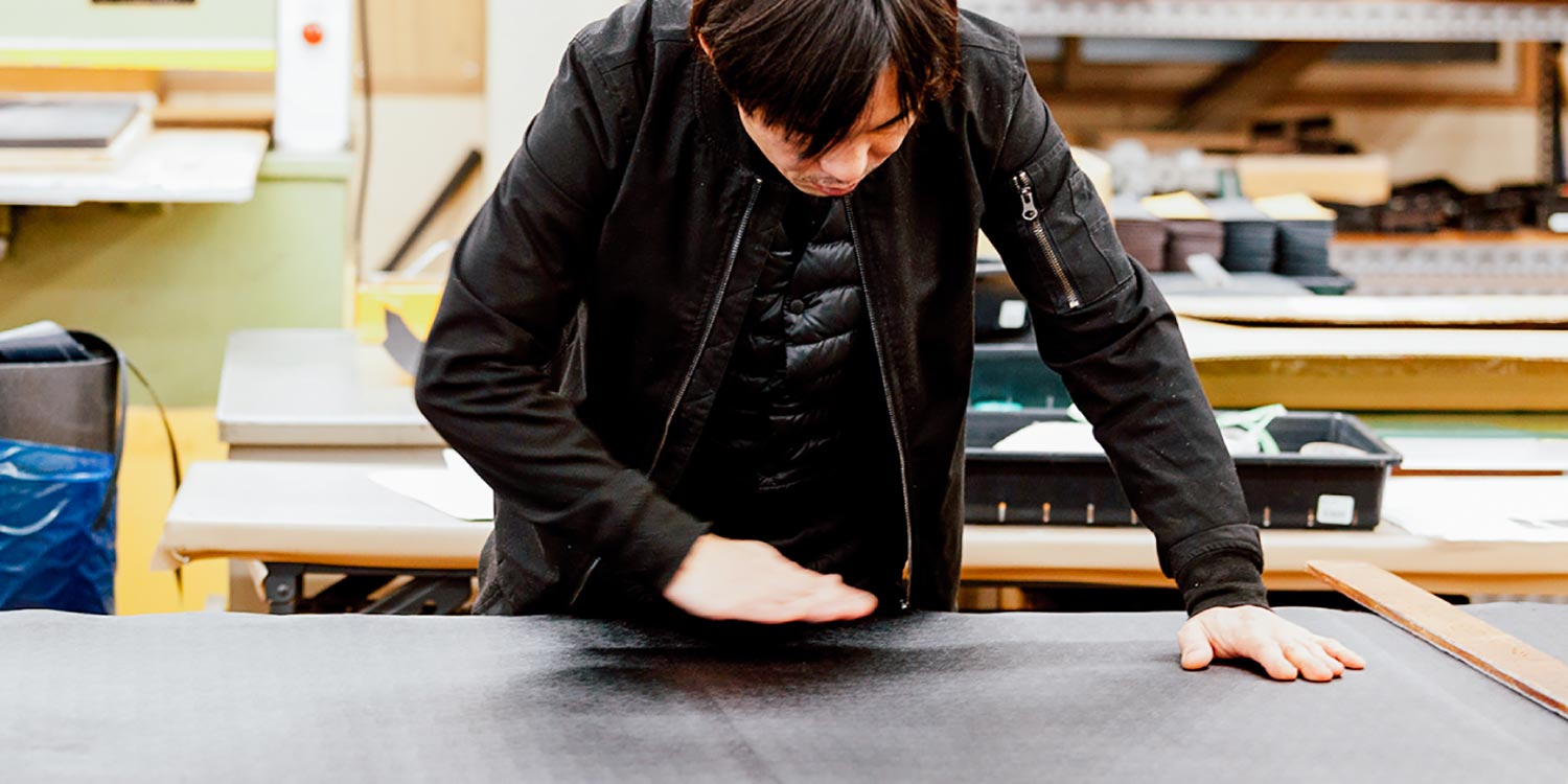 A craftsman preparing leather to make a Toyooka bag